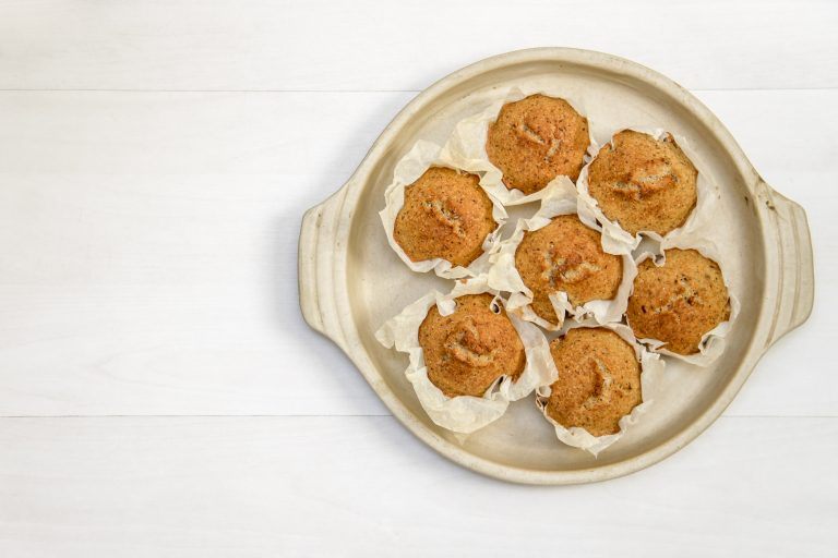 overhead shot of seven muffins on a circular ceramic tray
