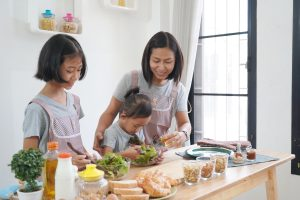 Mother and daughter cooking in the kitchen at home, happy family asian concept
