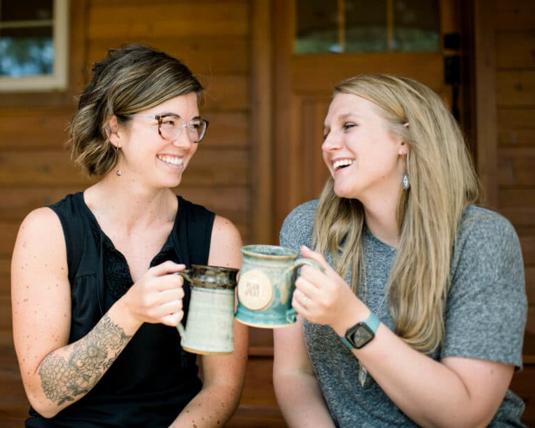 two young women smiling and clinking mugs together outside on a front porch