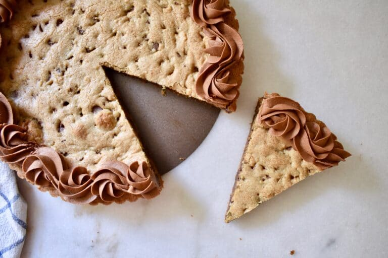 overhead shot of chocolate chip cookie cake with a slice cut out of it