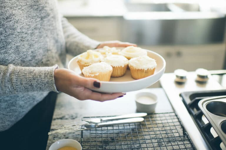cropped image of a woman holding a plate of frosted vanilla cupcakes