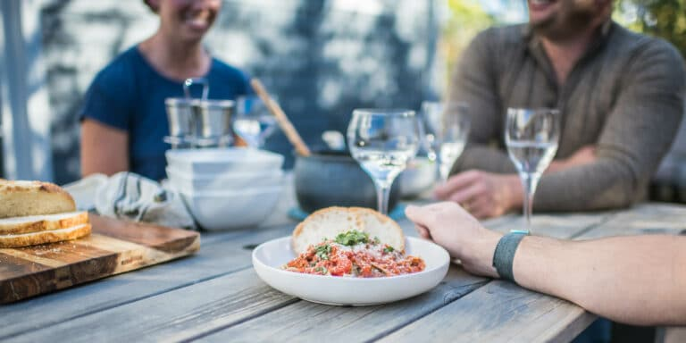 cropped image of dinner party with focus on plate of spaghetti and wine glasses